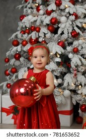Little girl is playing near Christmas tree