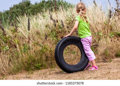 Little girl playing with old used rotten trash tire on dry summer grass.