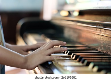 Little girl playing old vintage piano