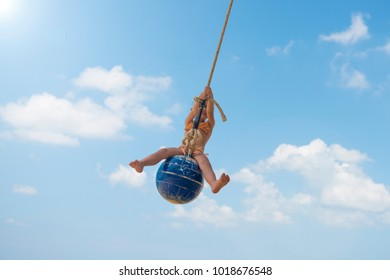 Little girl playing on the beach swing