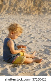 Little girl playing on the beach with sand.
