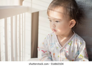 little girl playing on the bed in morning. A nice child girl enjoys sunny morning. Good morning at home. Child girl wakes up from sleep.