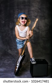 little girl playing on electric guitar on dark grunge background