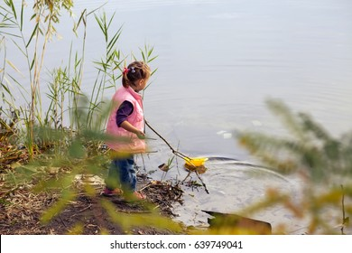A little girl is playing on the lake. She launches a yellow boat into the water.
