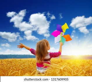 Little girl playing on the meadow on sun with windmill in her hands.  Child holding wind toy  on wheat field.