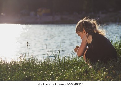 Little girl is playing on the river bank in summer at sunset