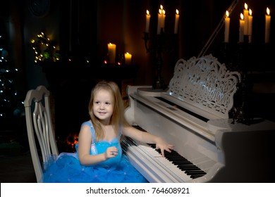 Little girl is playing on a white piano in a dark room by candlelight. Concept Christmas, New Year, holiday, family happiness, childhood.