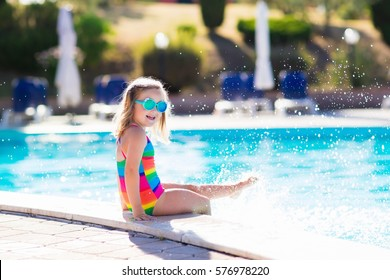 Little girl playing in outdoor swimming pool jumping into water on summer vacation on tropical beach island. Child learning to swim in outdoor pool of luxury resort. Water toy and sunglasses for kids