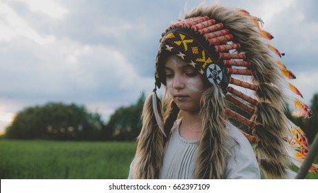Little girl playing outdoors in the field, wearing Indian headdress, pretending to be a native American