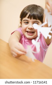 little girl playing with paper dolls