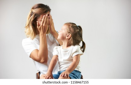 Little girl playing peekaboo game with her mother on white background with copy space. Woman and child are playing peek-a-boo and having fun. Parenthood and happy moments concept