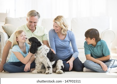 Little girl playing with pet dog while family looking at her in living room