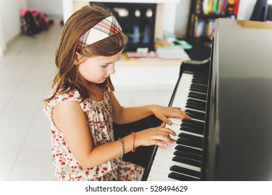 Little girl playing piano at home
