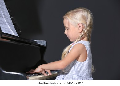 Little girl playing piano indoors