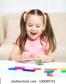 Little girl is playing with plasticine while sitting at table