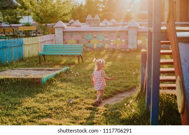 A little girl is playing in the playground in the bright sunset of the orange sun