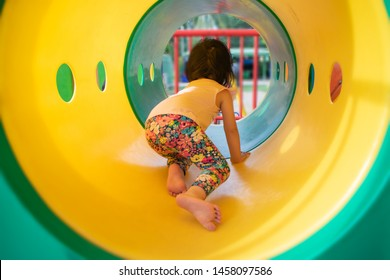 Little girl playing at playground. Child enjoying sunny summer or spring day outside.