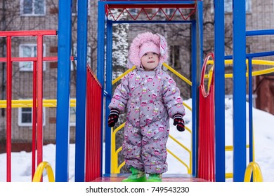 little girl is playing in the playground on a winter day