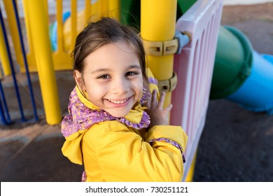 Little Girl Playing At Playground Outdoors In Autumn