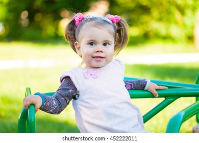 Little girl is playing in the playground in the park