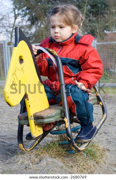 little girl playing at the playground with yellow pony