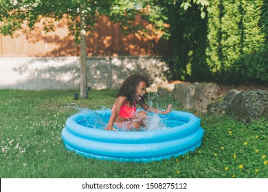 A little girl playing in a pool in the backyard.