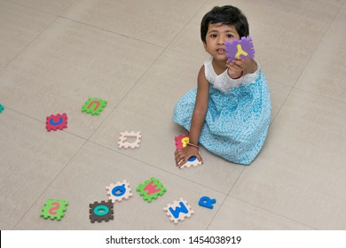 Little girl playing puzzle or Happy Girl playing or Indian girl playing with letter or abcd