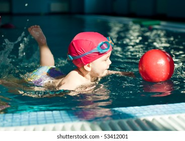 Little girl playing with red ball in a swimming pool