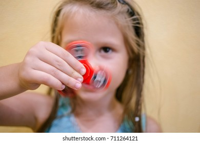 Little girl playing with red fidget spinner toy to relieve stress at home