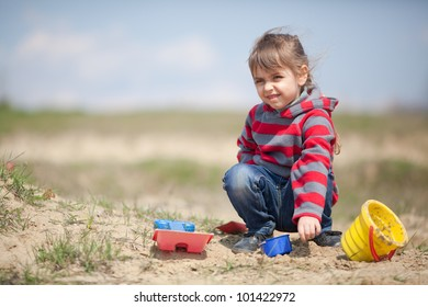 Little girl playing in the sand on the lake shore