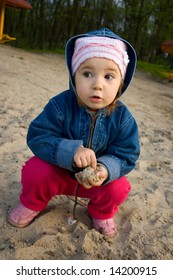little girl playing in sand on river back