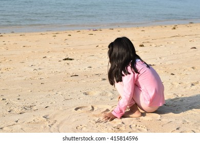 Little girl playing with sand on beach.