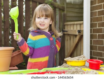 Little girl playing at a sand table in a garden, holding a spade and smiling