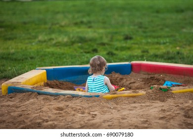 Little girl playing in the sandbox alone and away from everyone. Autism. The problem of communication.