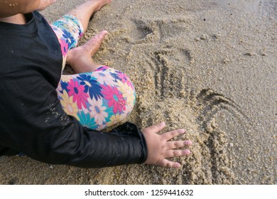 little girl playing sands on the beach during family vacation