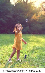 Little girl playing with soap balloons.Selective focus and small depth of field.