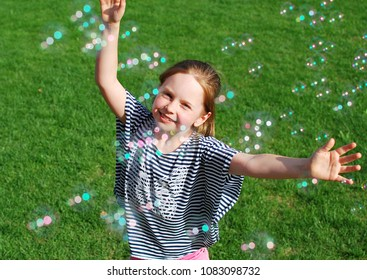 Little girl playing with soap bubbles. Cute smiling girl catching soap bubbles in the park on sunny day. Happy childhood.