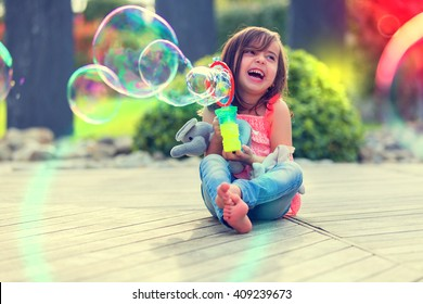 Little girl playing with soap bubbles machine