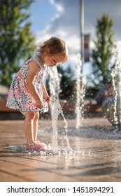 Little Girl Playing with Splash Fountain in Colorful Dress