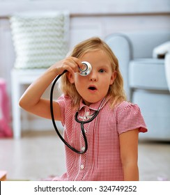 Little girl playing with stethoscope in the room