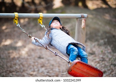 Little girl playing with a swing