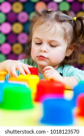 A little girl is playing at the table with colored plastic cups. Bright color background background. Selective focus