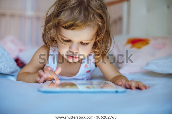 little girl playing tablet.