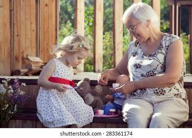 Little girl playing tea time with her grandmother on country house doorsteps in summer. Natural outdoor light setting.