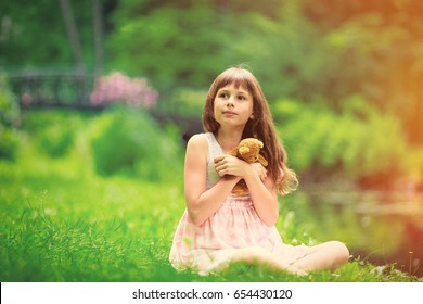 Little girl playing with teddy bear in park, Poland, Wroclaw