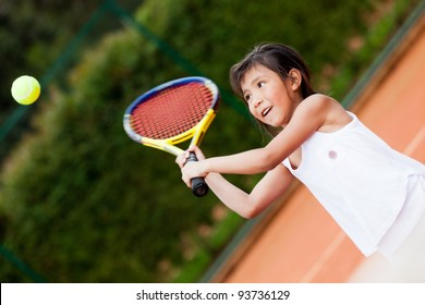 Little girl playing tennis at a clay court