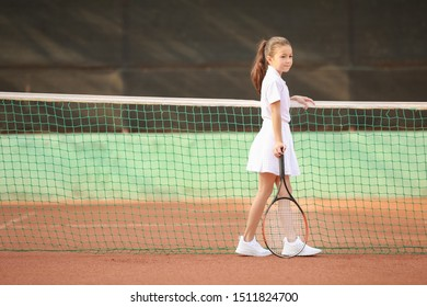 Little girl playing tennis on court