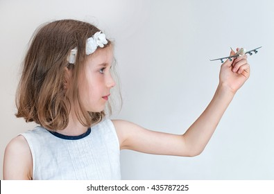 Little girl playing with toy airplane.