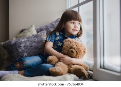 Little girl is playing with a toy bear on the window