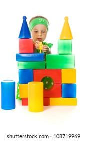Little girl is playing with toy cubes on a white background